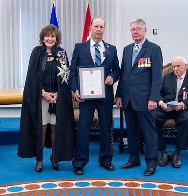 Arvid Thompson receives his Life-saving Award from Lt.-Gov. Lois E. Mitchell, at left, and John McDougall of St. John Ambulance.