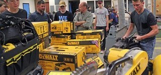 Proceeds from the 2018 Stanley & DeWALT Tool Enhancement Grant pile up in the Kate Andrews High School shop as teachers Daniel Griffith, left, and Rod Horlacher look on.