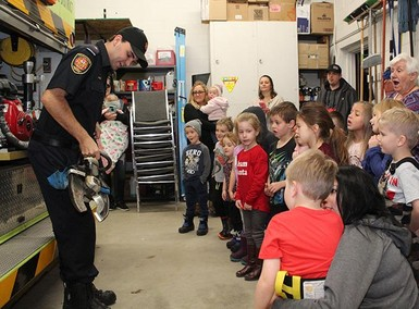 Firefighter Colby Stone shows JEES kindergarten students extrication tools during a tour of the Coaldale fire hall.