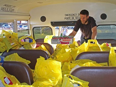 Teacher Kendell Wiens helps load up a bus as part of Kate Andrews High School's annual Community Food Drive.