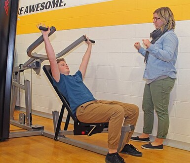 University practicum student Cidney Stinnissen shows a Coalhurst High School student how to use fitness equipment recently donated to the Palliser school.