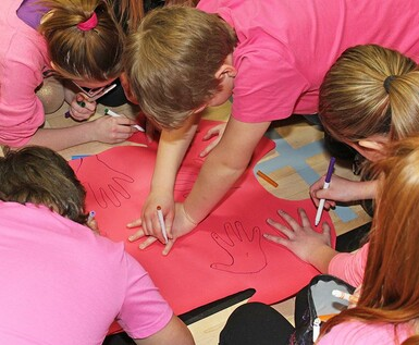 Noble Central School students decorate Pink Shirt Day T-shirt cut-outs.
