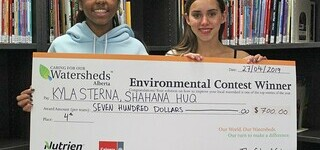Trinity Christian School Grade 9 students Kyla Sterna, left, and Shahana Huq, with a cheque for their fourth-place project in the 'Caring for Our Watersheds' competition.