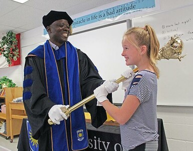 Chief marshal Olu Awosoga helps a Dororthy Dalgliesh School student heft the University of Lethbridge mace for a photo opportunity.
