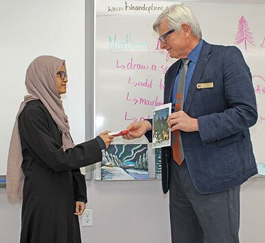 Trustee Don Boras thanks Akram Jomaa student Faoja Chowdhury for her winning greeting card submission.
