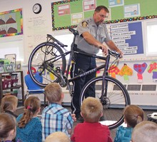 School resource officer Jerry Gurr shows some bike safety skills off to students at John Davidson School during Safety Day.