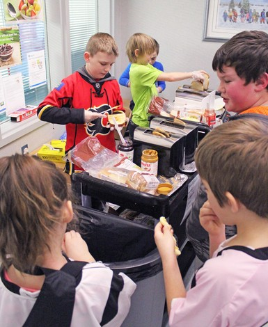 Dylan Campbell, left, and Killian Erick man the toasters on the Jennie Emery Elementary School breakfast carts, while 'runner' Jesse Hale helps out in the background.