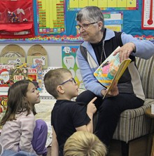 Beth Barclay, a former custodian at Coalhurst Elementary School, reads to a classroom of students following an assembly to celebrate the PAL program's 20th anniversary at the school.
