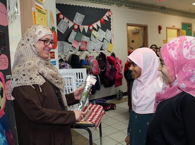 Students present a teacher with a rose as part of World Hijab Day at Calgary Islamic School Omar Bin Al-Khattab Campus
