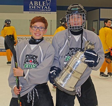 Students of R.I. Baker Middle School Hockey Academy hoist the Baker Cup after winning the annual staff-student hockey game in Coaldale.