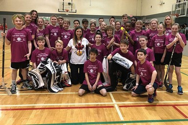 Former Olympian Chandra Crawford with floor hockey players at Calgary Christian School Elementary Campus.